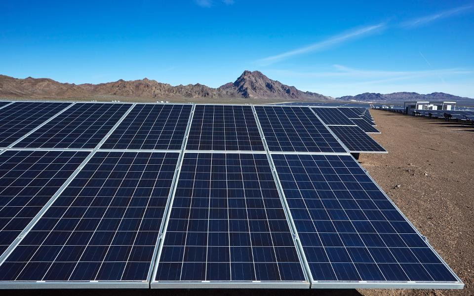 Solar panel installation in desert with mountains in background