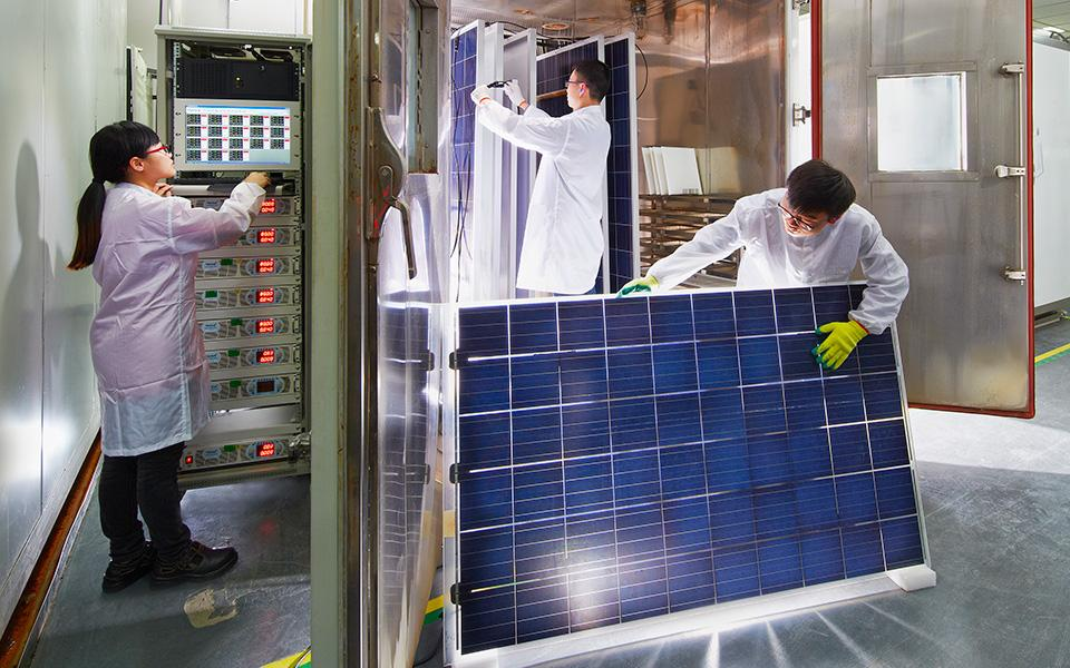 Factory workers handling solar module in research lab