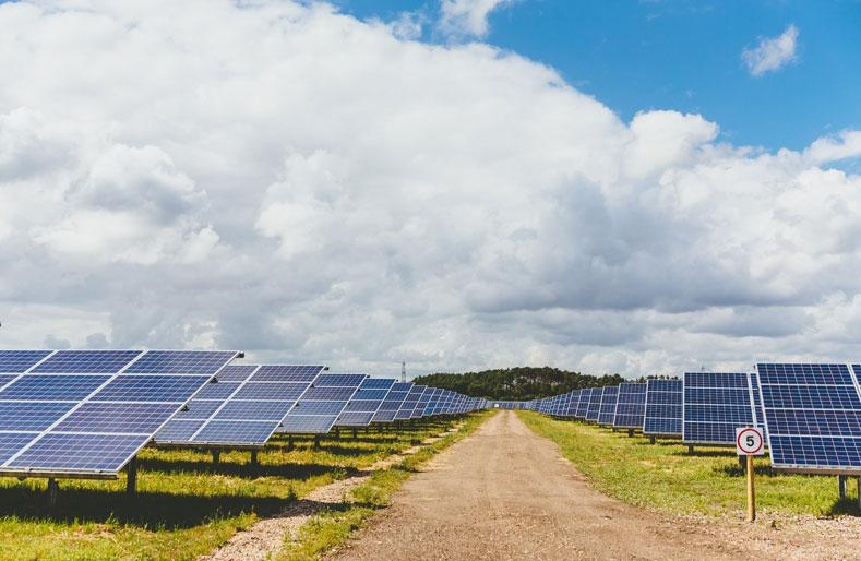 View solar installation with a dirt road in the middle and blue cloudy sky overhead